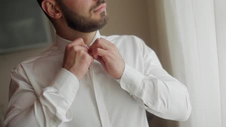 Man dressing close-up. Male hands button white shirt collar. No face positive bearded man puts on clothes and checks his look wear for going to work in the morning smiling happy