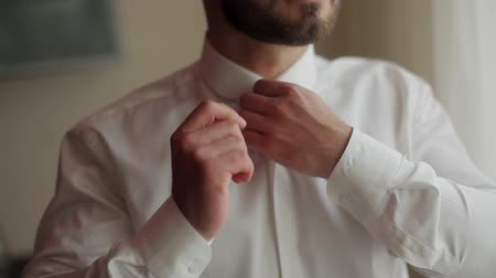 Man dresses buttoning shirt collar and puts hand in pocket close up no face. Putting on clothes and checking style for going to work or party. Macho establishment fashion lifestyle ready to go concept
