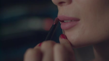 Professional eyes and lips make up close up slow motion. Makeup artist applying pin mat lipstick with brush to lips of model. False eyelashes eyes blinking grey shadow mascara product