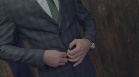 Unrecognizable stylish man dresses buttoning checked jacket and straightening it close up slow motion. Male clothing green tie casual fit expensive wearing vintage retro fashion sewing at tailors