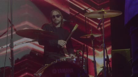 Drummer plays drums at concert in sunglasses slow motion close up. Long haired melancholic hangover rock musician star slowly performs drums set at stage at night. Alternative rock band performance Stock Footage