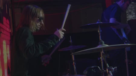 Rock star musician waves hair playing drums at stage slow motion side view close up. Drummer performing solo with drumsticks at concert at night club alternative band gig performance