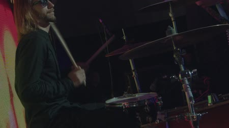 Man plays drums singing to microphone at concert stage slow motion close up. Backing vocals singer and alternative rock group performance in night club guitar playing at background