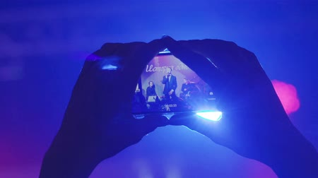 Female hands holding smart phone filming music band playing close up. Woman or girl makes video of singer performance on stage at concert with finger nails touching display. Quality gadgets technology Stock Footage