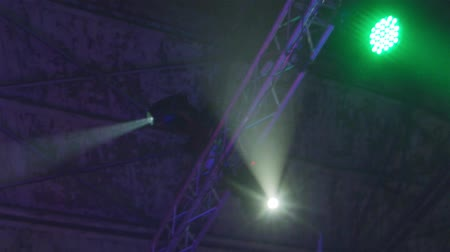 Different types of light equipment up ceiling slow motion. Lanterns and other led and halogen devices generate light beams illuminating hangar stage during rock festival
