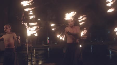 Fire performance in night street close up slow motion professional video. Two man twirling ignited poi with group of woman acrobats behind dance walking on stilts with burning fan torches