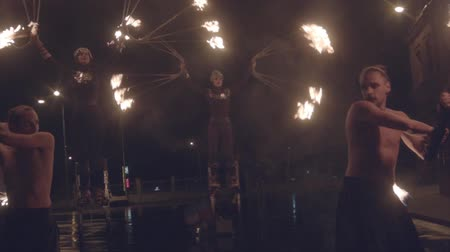 Fire performance in night street close up slow motion professional video. Two man twirling ignited poi with group of woman acrobats behind walking on stilts with burning fan torches