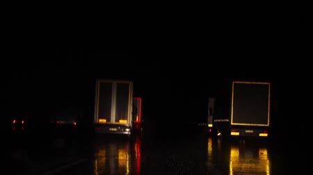 Driving night road at rain bad weather conditions and low visibility approaching parking lot with signs for truck drivers to stop by to rest from working hours. View from inside cabin at windscreen