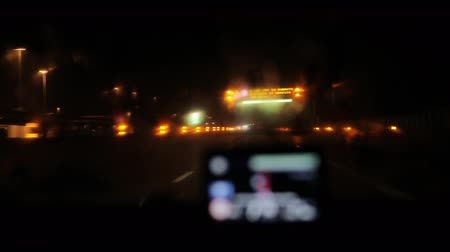 Night road from inside car 4k through defocused GPS navigation device screen. Passing electronic sign board with warning on wet slippery highway in Italy or Switzerland view from drivers perspective Stock Footage