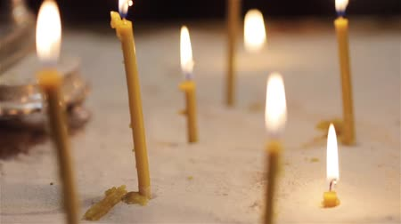 Burning candles church light macro close up. Many yellow wax candles glow with flame in sand near small altar in temple or cathedral. Orthodox religious rituals and ceremony faith worship concept