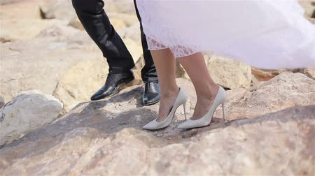 Male and female legs stand on stone windy day detail close up slow motion. Man in black leather shoes protects woman in white dress at Cannes seaside. Femininity glamour care withstand values concept Stock Footage