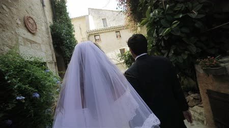 Newly wedded couple bride and groom back faceless walk old town narrow street slow motion. Woman in white dress and veil and man in black hold hands going to church together in Italy or France Europe Stock Footage