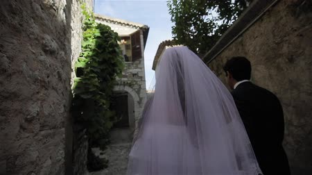 Newlyweds husband and wife walk unrecognizable down narrow street of ancient Italian town to get married slow motion. Young family bride go into future with fluttering veil holding hands with husband