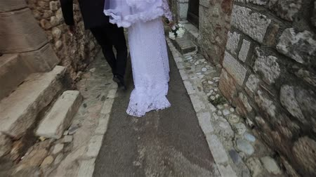 Newlywed couple bride and groom walk with only back seen down narrow street of ancient Italian or French town slow motion. Young wife wear white wedding dress with trail. Destination wedding in Europe