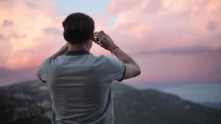 Man tourist traveller makes photos with phone for social network of clouds in top mountains slow motion close-up from back and side view. Connection communication 4g internet travel concept