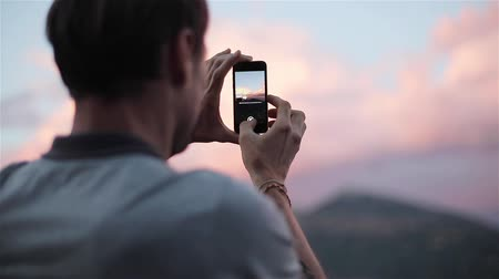Man traveller makes panoramic photo holding and turning phone standing on top of sunset mountain slow motion close up from back and side view. Technology travel fast mobile internet network connection Stock Footage