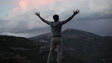 Man on top of mountain raising hands up succes slow motion shallow dof. Strong male silhouette holds hands up expressing inspiration reward determination achievement concept in Alps destination Europe