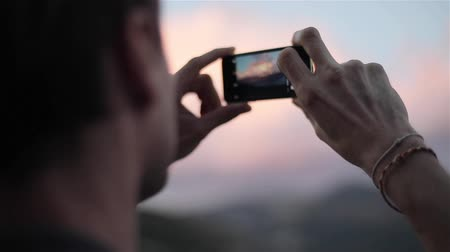 Male traveller takes photo with phone of pink clouds sky in mountains slow motion close up from back and side rack focus, looking for pictures touches screen focuses enjoys view and app possibilities Stock Footage
