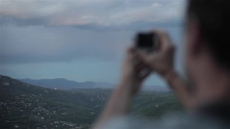Man shoots with camera in mountains slow motion close-up rack focus. Male traveller explorer makes video of picturesque evening hills valley in Europe with small camera for lifestyle experience vlog Stock Footage