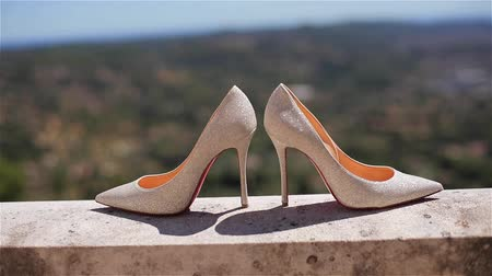 Woman shoes close up louboutins at green summer landscape shallow dof. Beautiful pair of stylish luxury bridal high-heeled white stiletto of material shining reflecting sun stand on balcony or terrace