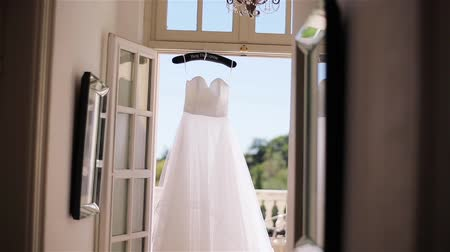 White dress hangs on special hanger in doorway to terrace close up. Light summer gown made of silk or chiffon fabrics waits for bride at sunny morning balcony. Wedding fashion tailoring design studio
