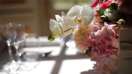 Menu carte empty glasses for wine water and pink flowers bouquet on white tablecloth arranged for fine dining tracking macro close-up. Festive elegant table set for eating at restaurant cafe banquet