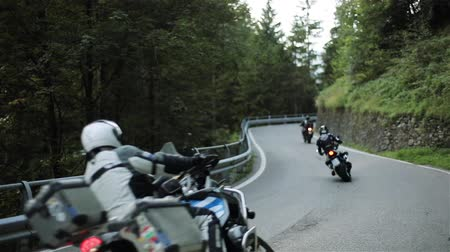 Motorcycle riders ride bikes mountain wood road up one by one slowly. Group of unrecognizable men motorcyclists on motorbikes in helmets protection suits drive twisting serpentine road lane with rails Stock Footage