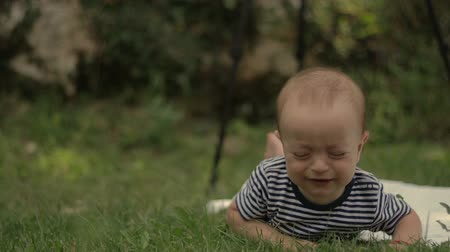 full bucket : A small child lies on the grass grins and plays close-up