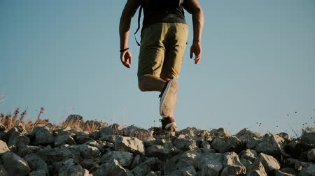 определение : A man with a large backpack is climbing a mountain.Young man Practicing Healthy Active Lifestyle.