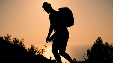 определение : A man with a backpack rises to the top of the mountain at sunset. Silhouette of the person at sunset. Healthy Active Lifestyle.