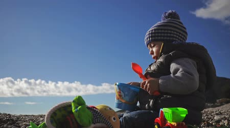listens : A small child plays with toys on the sea shore in winter clothes and a hat. Stock Footage