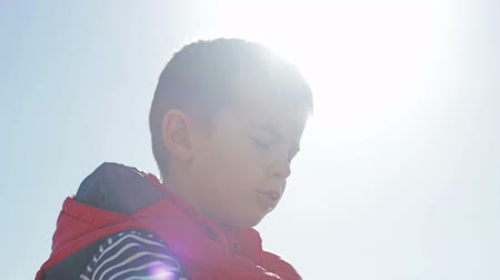 raios de sol : Boy looks high in the sky. Closeup.