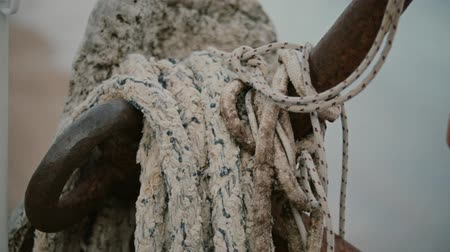 hawser : Old rusty anchor with coiled ropes