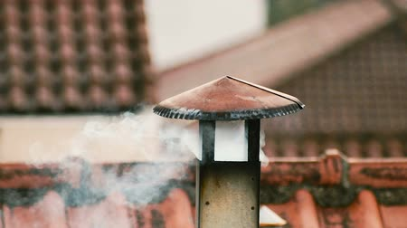 дымоход : Smoke comes from the chimney of the house. The pipe on the roof. Chimney. Country house. The house with a chimney. Smoke on the background of roofs Стоковые видеозаписи