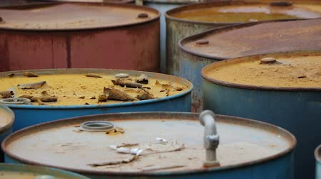 потреблять : Old rusty barrels with oil products casks