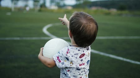 eye ball : Little boy is holding the ball in his hands on the football field