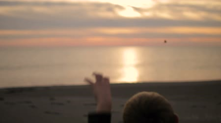 oturur : The boy sits on the beach at sunset and throws a stone into the sea. Stok Video