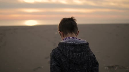 şaşırtıcı : The boy walks along the beach at sunset.