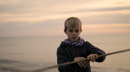каратэ : The boy turns the stick in his hands while standing on the beach at sunset.