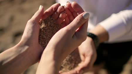sifted : The girl pours sand in mans hands