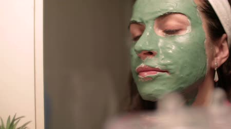 mimos : Beautiful woman with facial mask. Spa therapy for young woman receiving facial mask.