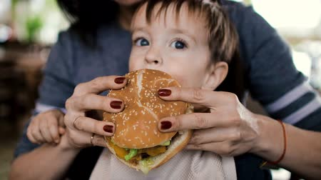 bacon burger : Mum feeds the child a tasty hamburger, cheeseburger