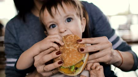 molho de tomate : Mum feeds the child a tasty hamburger, cheeseburger
