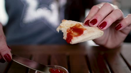 hranolky : The girl holds bread in her hands and spreads ketchup or sauce on it.
