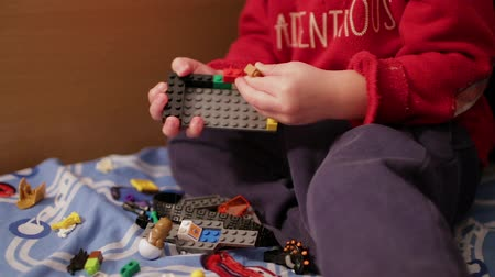 lego : A child playing in the childrens designer on the bed