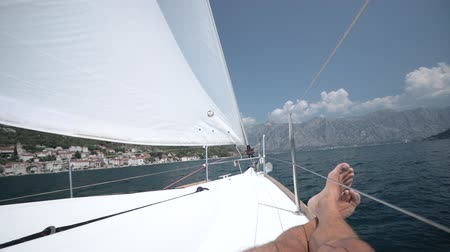 kap : A man on a sailing yacht lies on the deck and gets pleasure The wind blows into a sail Stock mozgókép