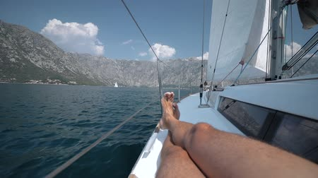 регата : A man on a sailing yacht lies on the deck and gets pleasure The wind blows into a sail Стоковые видеозаписи