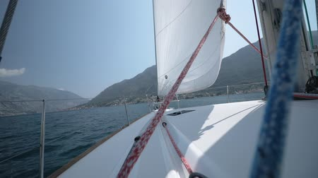 регата : Turn the sailing yacht, change the sail and the direction of movement against the backdrop of beautiful mountains and blue sky