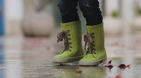 yelow : Little boy in rubber boots stands in a puddle during the rain