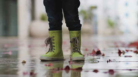 mókás : Little boy in rubber boots stands in a puddle during the rain